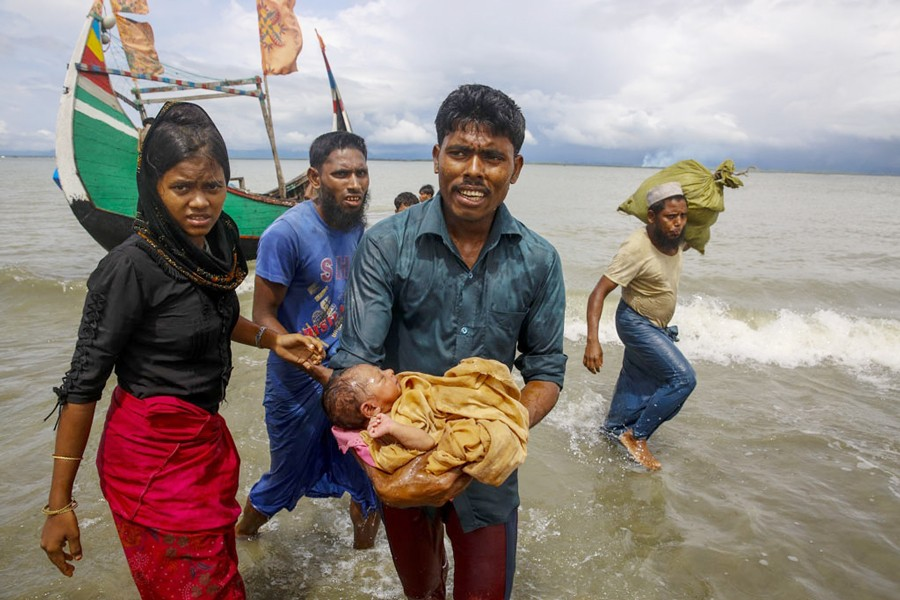 A file photo showing a Rohingya man carrying an infant to the shore from a boat that arrived at Shah Porir Dwip in Bangladesh from Rasidong in Myanmar recently. A US government investigation has found that Myanmar's military waged a planned, coordinated campaign of mass killings, gang rapes and other atrocities against the Southeast Asian nation's Rohingya Muslim minority— Reuters