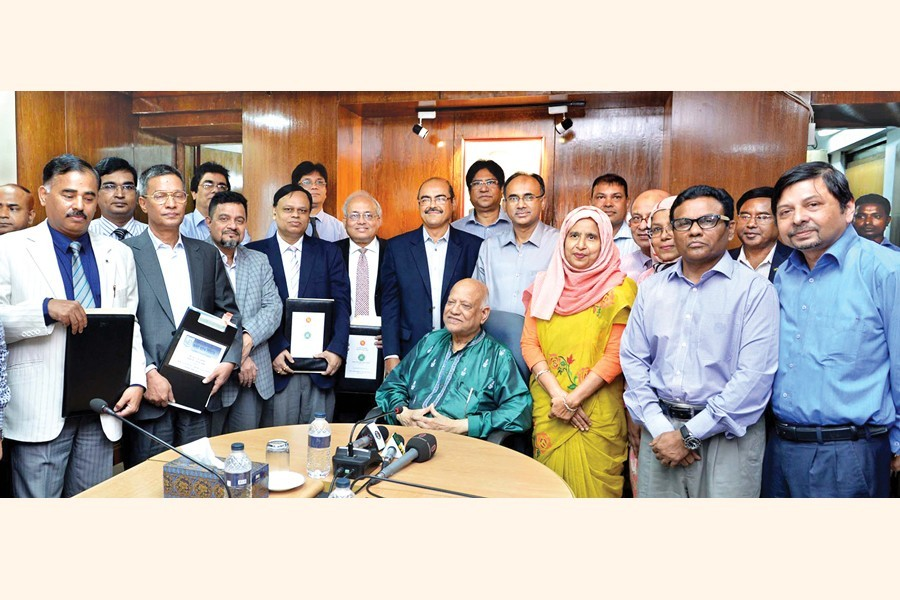 Top officials of Sonali Bank, Janata Bank, Agrani Bank, Rupali Bank and the Bangladesh House Building Finance Corporation posing with Finance Minister AMA Muhith at the signing ceremony of a memorandum of understanding on home loans with the finance ministry at the conference room of the ministry in the city on Tuesday — PID photo