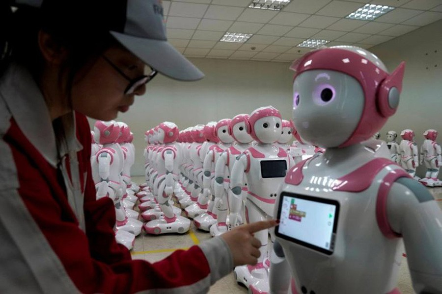 A worker puts finishing touches to an iPal social robot, designed by AvatarMind, at an assembly plant in Suzhou, Jiangsu province, China, July 4, 2018. Reuters/File Photo