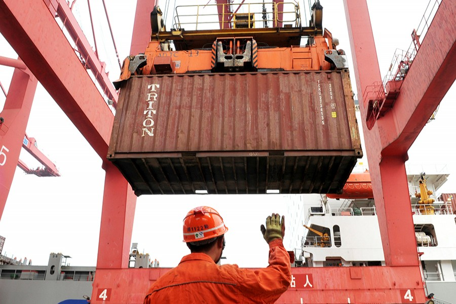 An employee guides a crane as it unloads shipping containers from a cargo ship at a port in Lianyungang, Jiangsu province on March 8, 2014 — Reuters/File