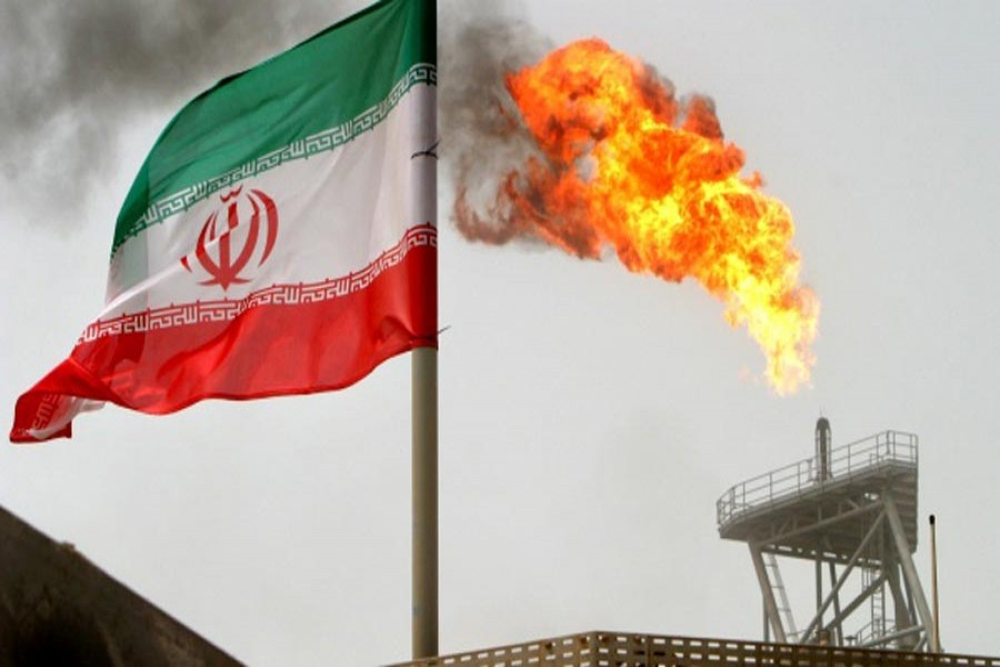 A gas flare on an oil production platform in the Soroush oil fields is seen alongside an Iranian flag in the Persian Gulf, Iran       — Reuters