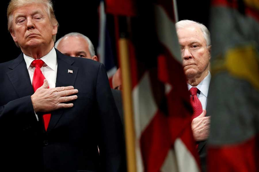 US President Donald Trump and Attorney General Jeff Sessions stand for the national anthem at a graduation ceremony at the FBI Academy on the grounds of Marine Corps Base Quantico in Quantico, Virginia, US, December 15, 2017. Reuters/File Photo