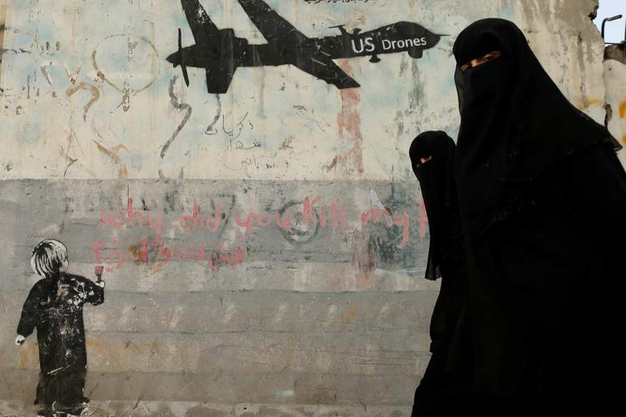 Women walk past a graffiti, denouncing strikes by US drones in Yemen, painted on a wall in Sanaa, Yemen February 6, 2017. Reuters/Files
