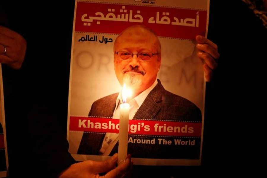 A demonstrator holds a poster with a picture of Saudi journalist Jamal Khashoggi outside the Saudi Arabia consulate in Istanbul, Turkey October 25, 2018 - Reuters