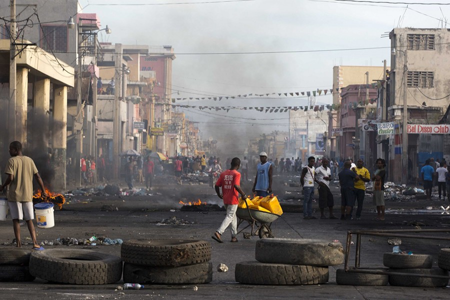 Residents walk amid road blocks placed by anti-government protesters along Boulevard Jean-Jacques Dessalines, a main commercial artery, during a strike against alleged government corruption in Port-au-Prince, Haiti on Wednesday — AP photo
