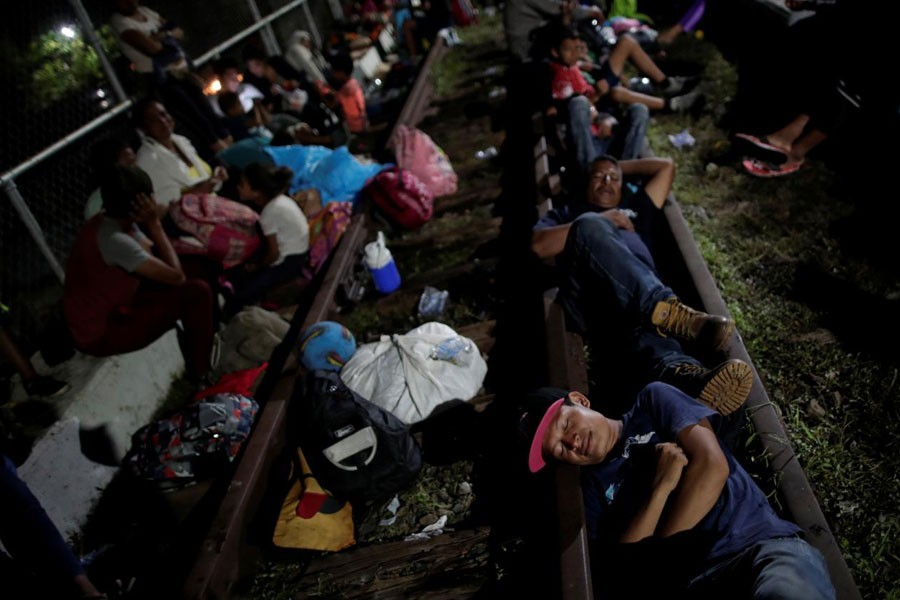 Honduran migrants, part of a caravan trying to reach the US, rest on the bridge that connects Mexico and Guatemala in Ciudad Hidalgo, Mexico, October 19, 2018 - Reuters