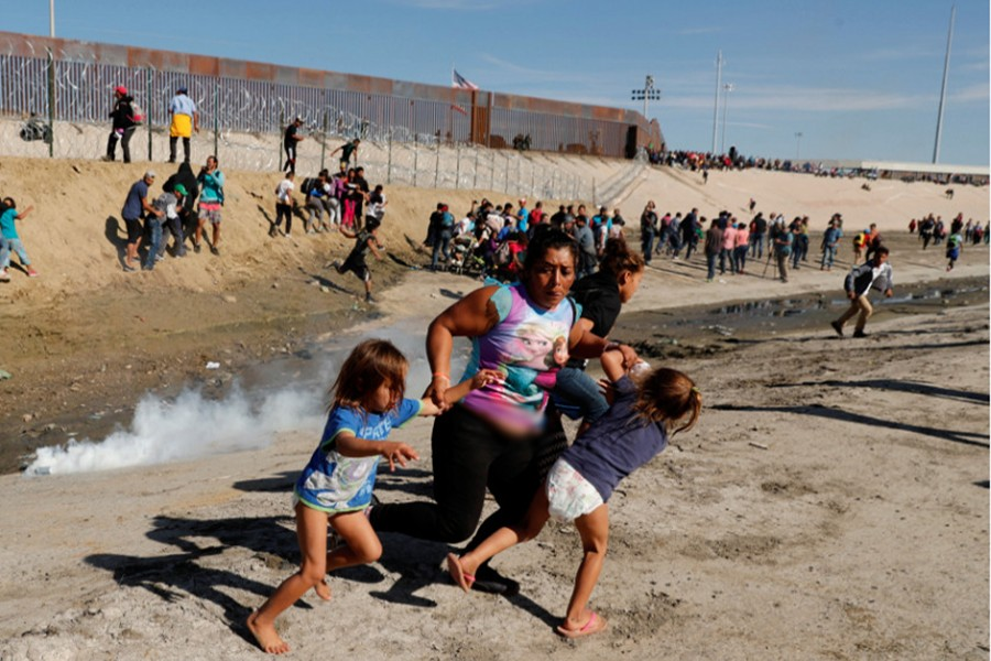 A migrant family, part of a caravan of thousands traveling from Central America en route to the United States, run away from tear gas in front of the border wall between the US and Mexico in Tijuana, Mexico on Monday — Reuters photo