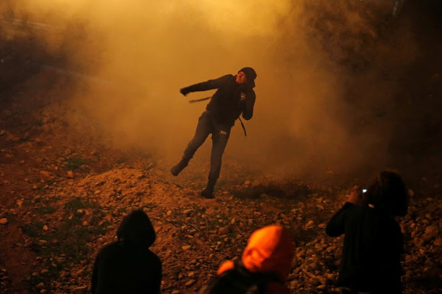 A migrant, part of a caravan of thousands from Central America trying to reach the United States, throws back a tear gas bomb after US Customs and Border Protection (CBP) throw tear gas to the Mexican side of the fence as they prepared to cross it illegally, in Tijuana, Mexico, January 1, 2019 - REUTERS/Mohammed Salem