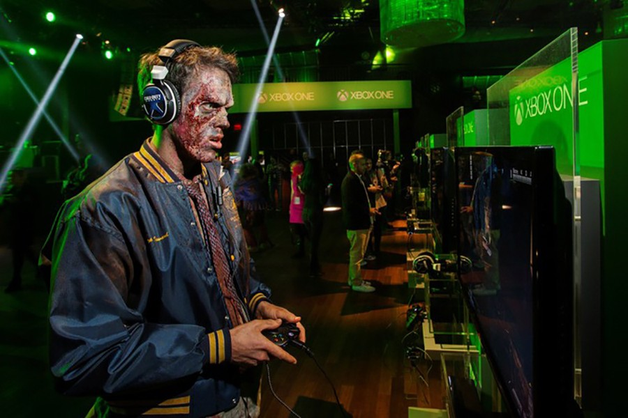 A man dressed as a zombie plays video games on an Xbox One console during a midnight launch event in New York, November 21, 2013. Reuters/File photo