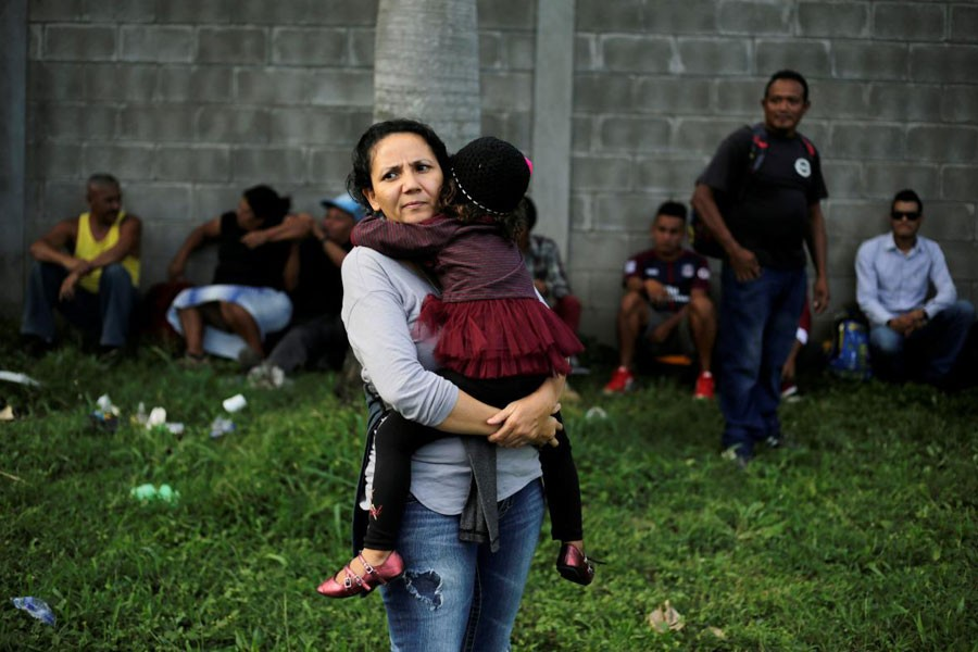 A Honduran woman carries her daughter as they wait to leave with a new caravan of migrants, set to head to the United States, at a bus station in San Pedro Sula, Honduras, January 14, 2019 - REUTERS/Jorge Cabrera