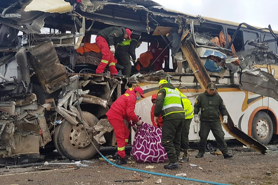 In this photo released by the Bolivian Police of Oruro, firefighters and police help a victim of a crash of two buses on the outskirts of Challapata, Bolivia on Saturday — via AP