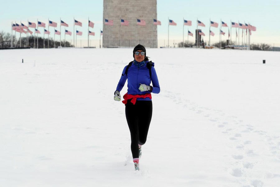 A jogger makes her way through snow at the Washington Monument following a winter storm, January 14, 2019. Reuters/File Photo