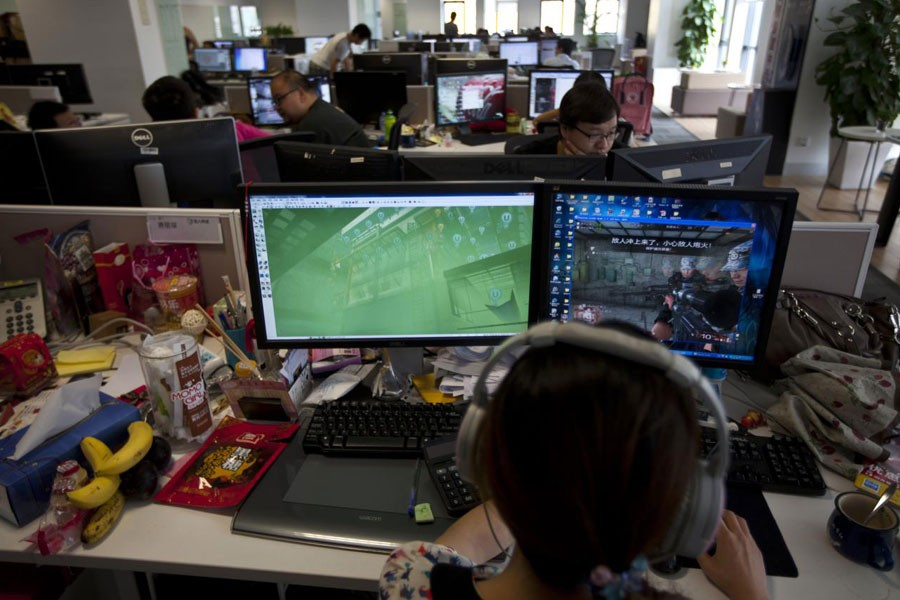 """FILE PHOTO: An employee watches a computer screen displaying the video game """"Glorious Mission Online"""" at the game developer's office in Shanghai August 2, 2013 - REUTERS/Aly Song"""