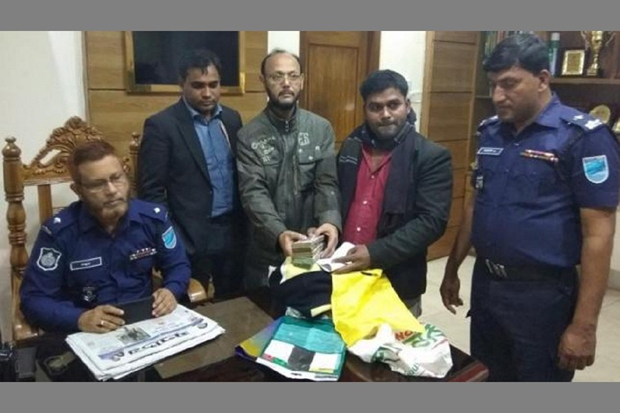 Sarwar Jahan, a bank official deposits the bag at the Fatullah Model Police Station to find out the owner of the money. Photo: Courtesy