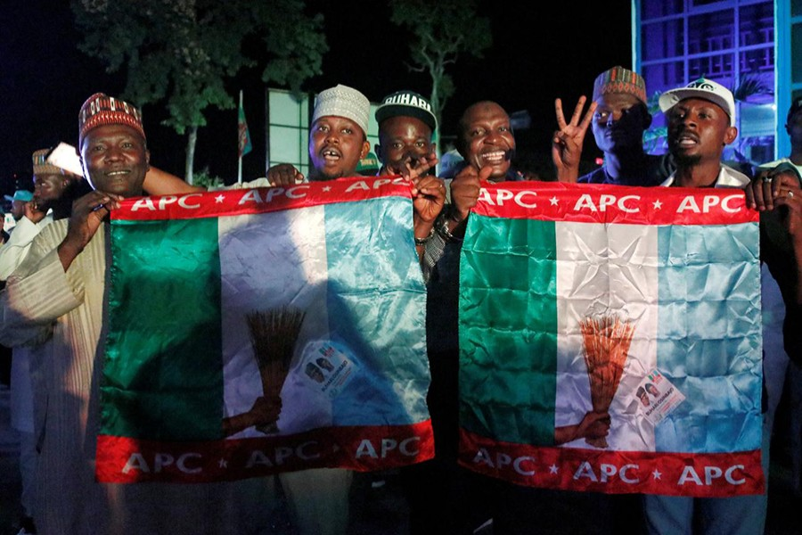 Supporters of Nigeria's President Muhammadu Buhari carry APC flags as they celebrate at the campaign headquarters of All Progressives Congress (APC) in Abuja, Nigeria on Tuesday — Reuters photo