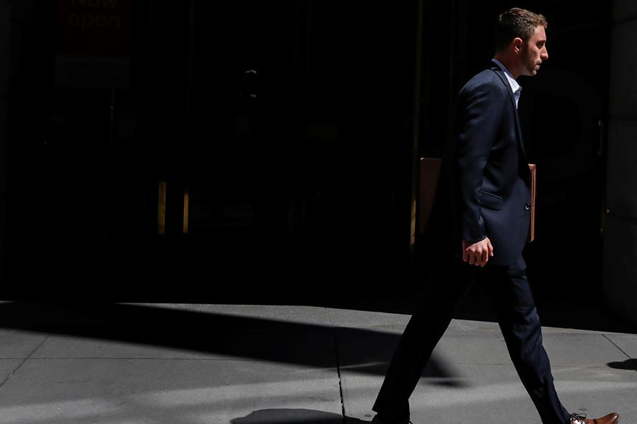 A man in a suit walks on Wall St in New York City, US, August 23, 2018 - REUTERS/Brendan McDermid