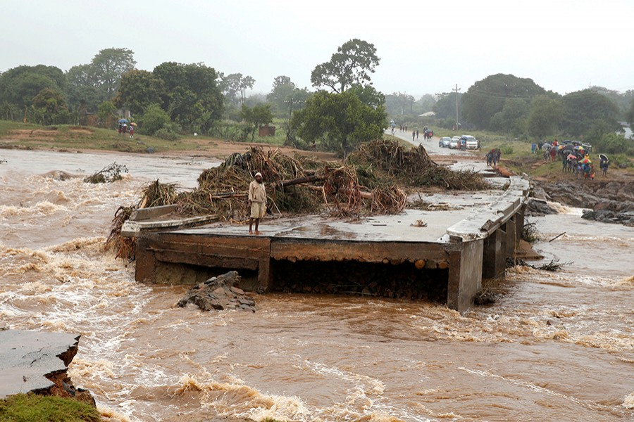 A man looks at a washed away bridge along Umvumvu river in Chimanimani, Zimbabwe on March 18, 2019 — Reuters photo