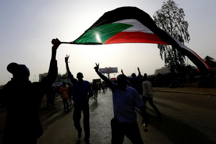 Sudanese demonstrators wave their national flag as they arrive for a protest rally demanding Sudanese President Omar Al-Bashir to step down outside the Defence Ministry in Khartoum, Sudan April 11, 2019 - REUTERS/Stringer