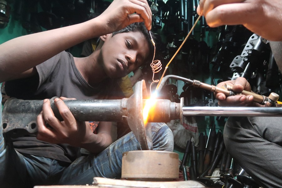 A boy  working at a light engineering workshop in Old Dhaka recently  	— FE photo by Shafiqul Alam