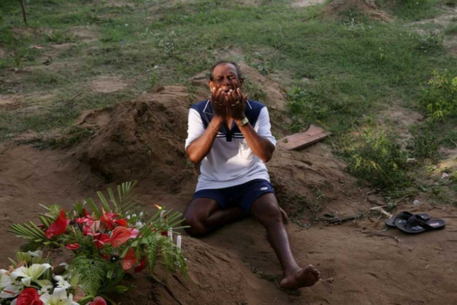 A man mourns at a grave of a victim, two days after a string of suicide bomb attacks on churches and luxury hotels across the island on Easter Sunday, at Sellakanda Catholic cemetery in Negombo, Sri Lanka April 23, 2019. - Reuters