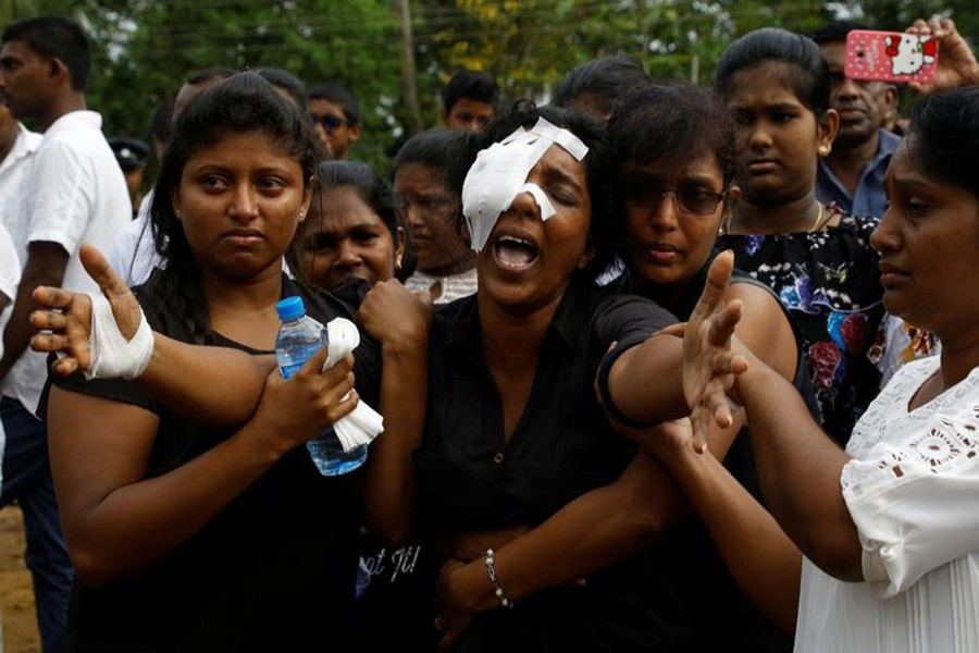 Kumari Fernando, who lost her husband, Dulip Fernando, and two children, Dulakghi and Vimukthi, during the bombing at St Sebastian's Church, yells towards the graves during a mass burial for victims at a cemetery near the church in Negombo in Sri Lanka, April 24, 2019. Reuters