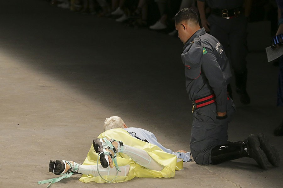 Model Tales Soares lies on the catwalk as a paramedic tends to him after he collapsed during Sao Paulo Fashion Week in Sao Paulo, Brazil, Saturday, April 27, 2019. A statement from organisers said that Soares died after taking ill while participating in the Sao Paulo's Fashion Week -Leco Viana/Thenews2 via AP