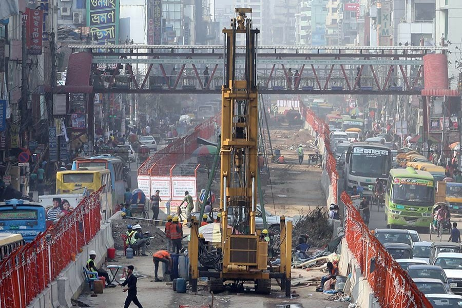 Metro-rail construction squeezes the scope of vehicular movement on the busy road from Mirpur to Agargaon in the capital, intensifying gridlock in the areas.— FE Photo by KAZ Sumon