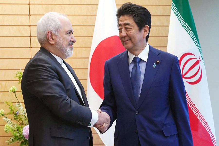Iranian Foreign Minister Mohammad Javad Zarif, left, and Japanese Prime Minister Shinzo Abe, right, shake hands at Abe's official residence in Tokyo Thursday, May 16, 2019. Eugene Hoshiko/Pool via Reuters