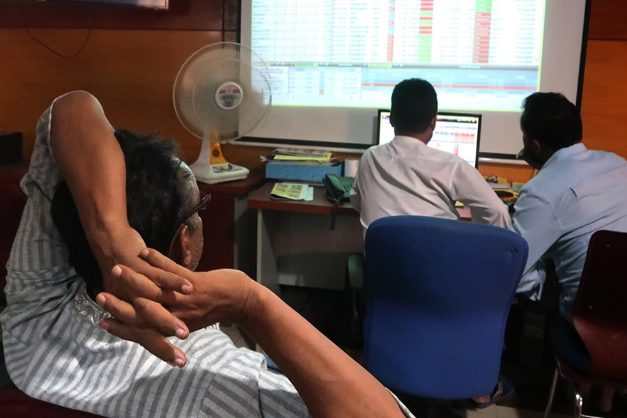 Investors monitoring stock price movements on computer screens at a brockerage house in the capital city — FE/Files