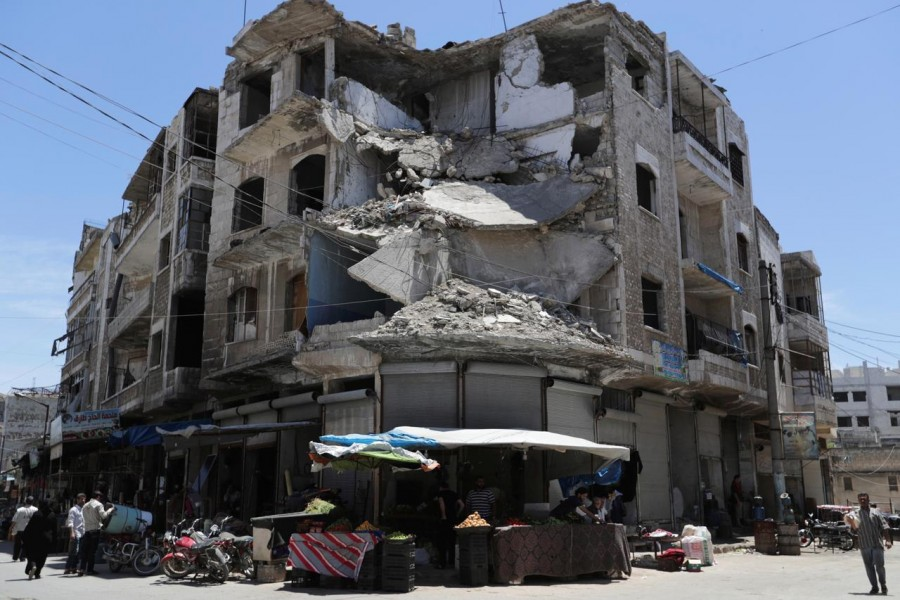 People walk past a damaged building in the city of Idlib, Syria May 25, 2019 - REUTERS/Khalil Ashawi