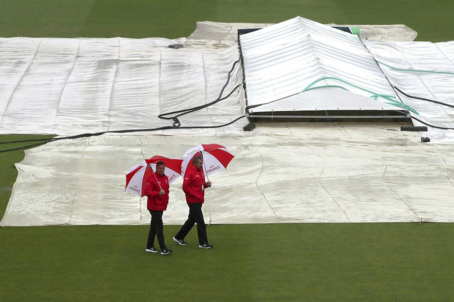 Umpires Richard Illingworth (right) and Richard Kettleborough inspect the field of play as it continues to rain at the ICC Cricket World Cup group stage match at the County Ground in Bristol, England on Tuesday, June 11, 2019. The Bangladesh side were scheduled to play with Sri Lanka on the day, but the match was later abandoned without a boll being bowled after persistent rain in the city — AP photo