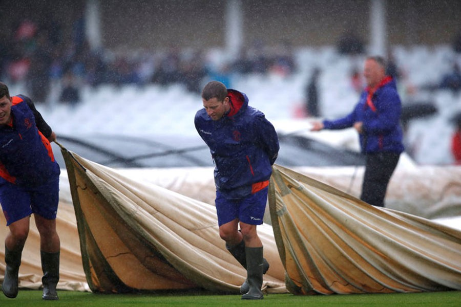 Ground staff putting covers on the pitch as rain delays a match, India v New Zealand, at Trent Bridge in Nottingham of Britain on June 13, 2019. -Reuters file photo