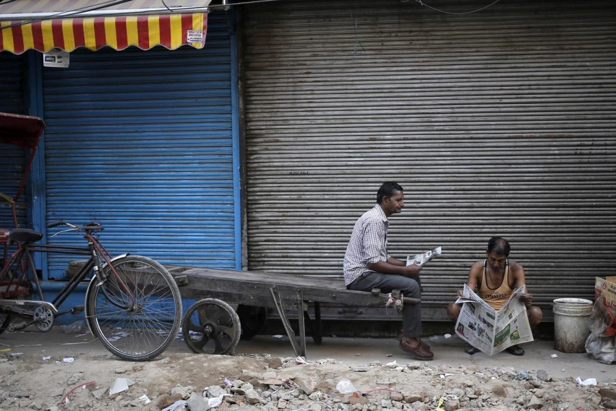 Labourers read newspapers in front of a closed shop in the old quarters of Delhi, India, March 29, 2016. Reuters/File Photo
