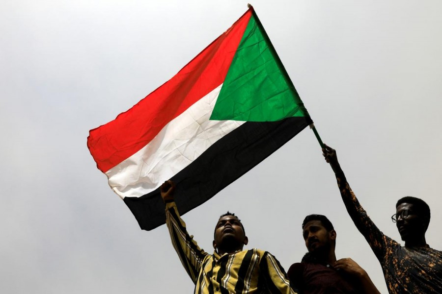 Demonstrators hold Sudanese flag as they march on the streets demanding the ruling military hand over to civilians, in Khartoum, Sudan, June 30, 2019 - REUTERS/Umit Bektas
