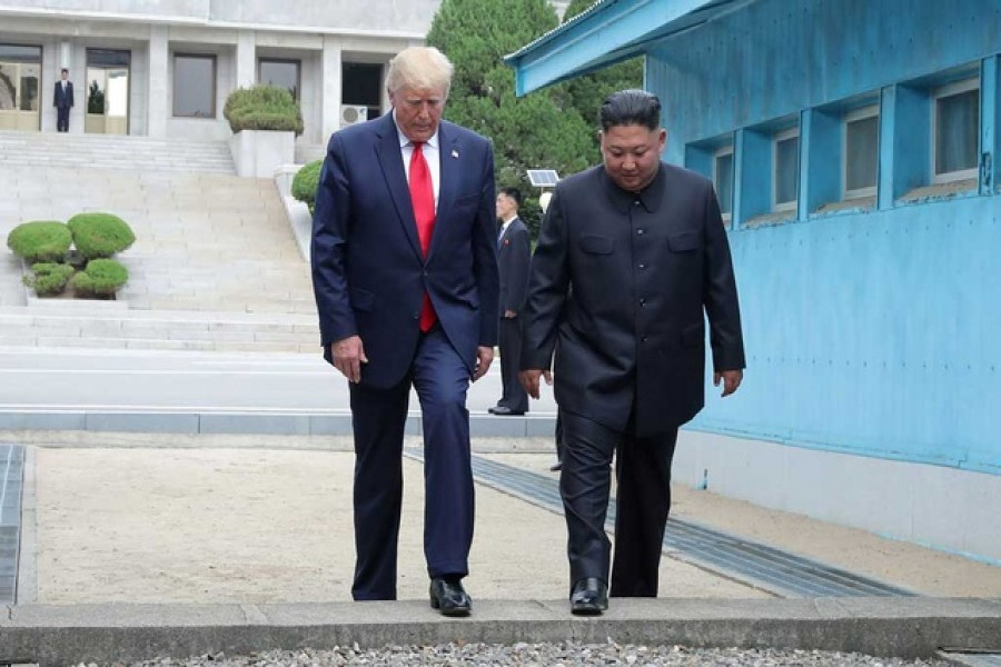 Trump-Kim meeting: US President Donald Trump and North Korean leader Kim Jong Un cross over a military demarcation line at the demilitarised zone (DMZ) separating the two Koreas, in Panmunjom, South Korea, June 30, 2019. KCNA via Reuters