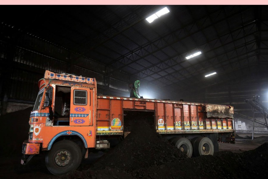 A worker shovels coal in a supply truck at a yard on the outskirts of Ahmedabad, India, October 25, 2018. Reuters/File Photo