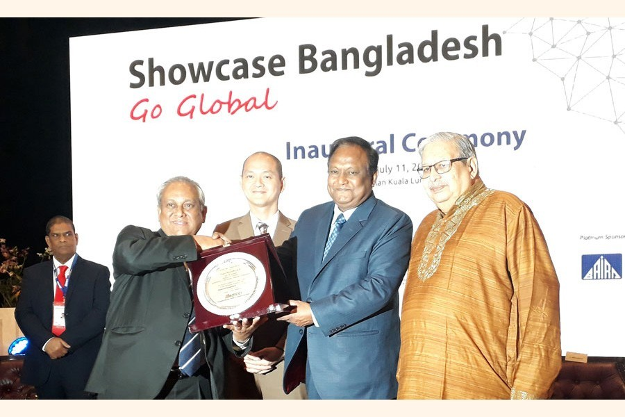 Bangladesh-Malaysia Chamber of Commerce and Industry president Syed Moazzam Hossain hands over a crest to commerce minister Tipu Munshi at the inaugural session of a programme styled 'Showcase Bangladesh-Go Global' in Kuala Lumpur on Thursday