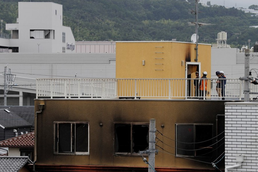Firefighters are seen checking an entrance at the rooftop of the torched Kyoto Animation building in Kyoto