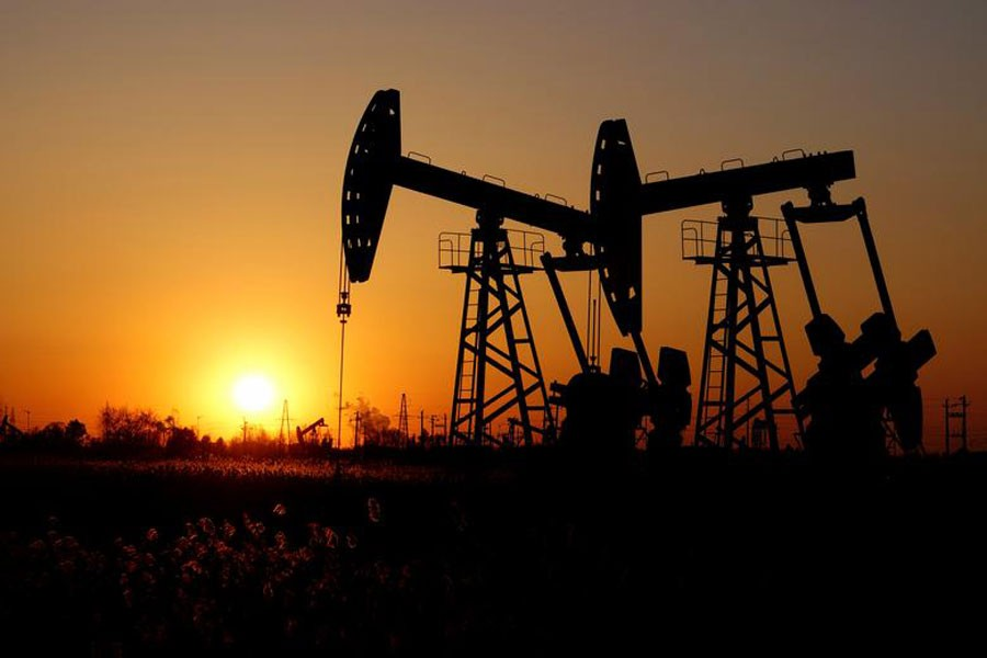 Pumpjacks are seen against the setting sun at the Daqing oil field in Heilongjiang province, China             	—  Reuters