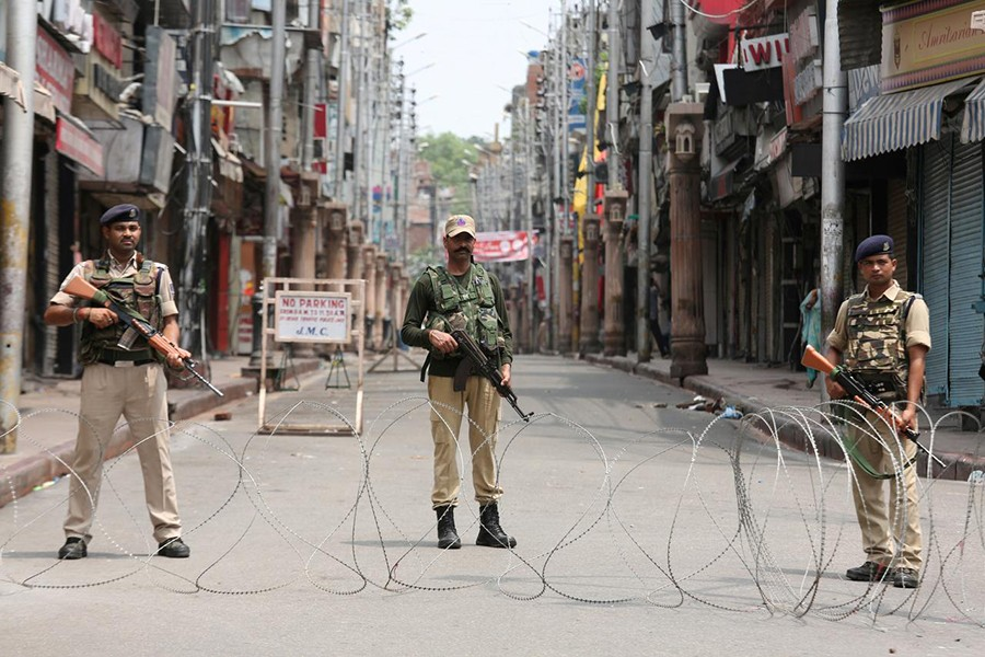 Indian security personnel stand guard along a deserted street during restrictions in Jammu on August 5, 2019 — Reuters photo