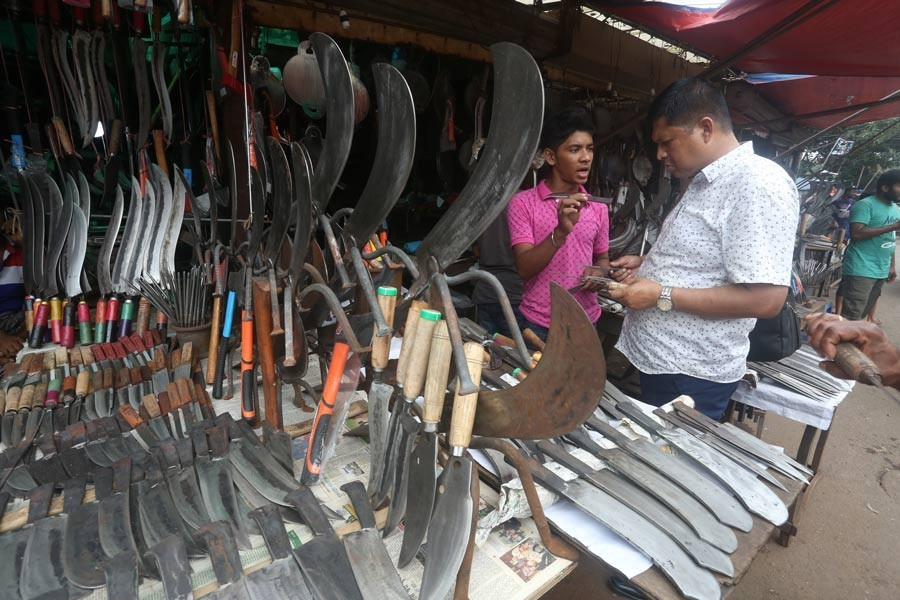 A customer is making a choice of slaughtering tools at a shop in the city's Karwan Bazar on Wednesday as the trader displayed a good collection of the equipment ahead of the Eid-ul-Azha — FE Photo