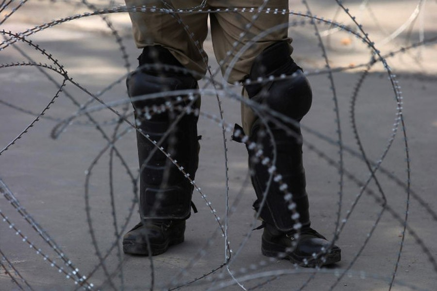 An Indian police officer stands behind the concertina wire in Srinagar, August 12, 2019 (Reuters