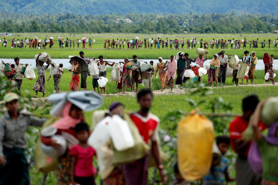 Rohingya refugees, who crossed the border from Myanmar two days before, walk after they received permission from the Bangladeshi army to continue on to the refugee camps, in Palang Khali, near Cox's Bazar, Bangladesh, October 19, 2017. Reuters/File Photo