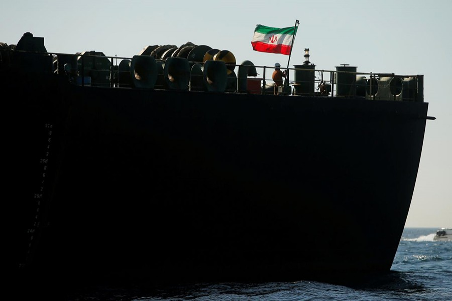 A crew member raises the Iranian flag on Iranian oil tanker Adrian Darya 1, previously named Grace 1, as it sits anchored after the Supreme Court of the British territory lifted its detention order, in the Strait of Gibraltar, Spain on August 18, 2019 — Reuters photo