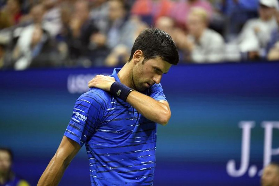 Novak Djokovic of Serbia rubs his shoulder during a match against Stan Wawrinka of Switzerland in the fourth round on day seven of the 2019 US Open tennis tournament at USTA Billie Jean King National Tennis Center — Danielle Parhizkaran-USA TODAY Sports via REUTERS