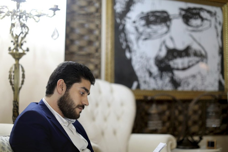 Abdullah Mursi, the youngest son of Egypt's ousted Islamist President Mohamed Morsi, sits in front of a framed image of his father that was printed on a flag during the 2013 Rabaah al-Adawiya sit-in, at his home in Cairo, Egypt — AP/Files