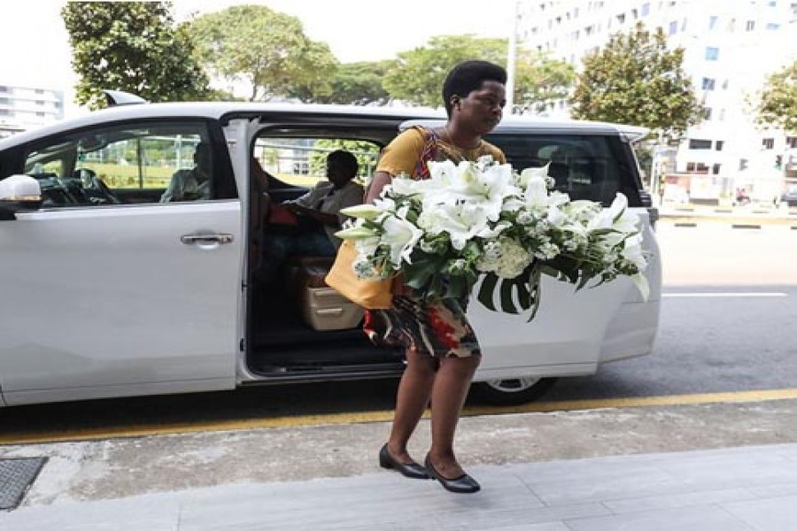 A visitor arrives with a wreath at the Singapore Casket funeral parlor building where the body of Robert Mugabe was being held on September 07, 2019, in Singapore.         — Photo: AP