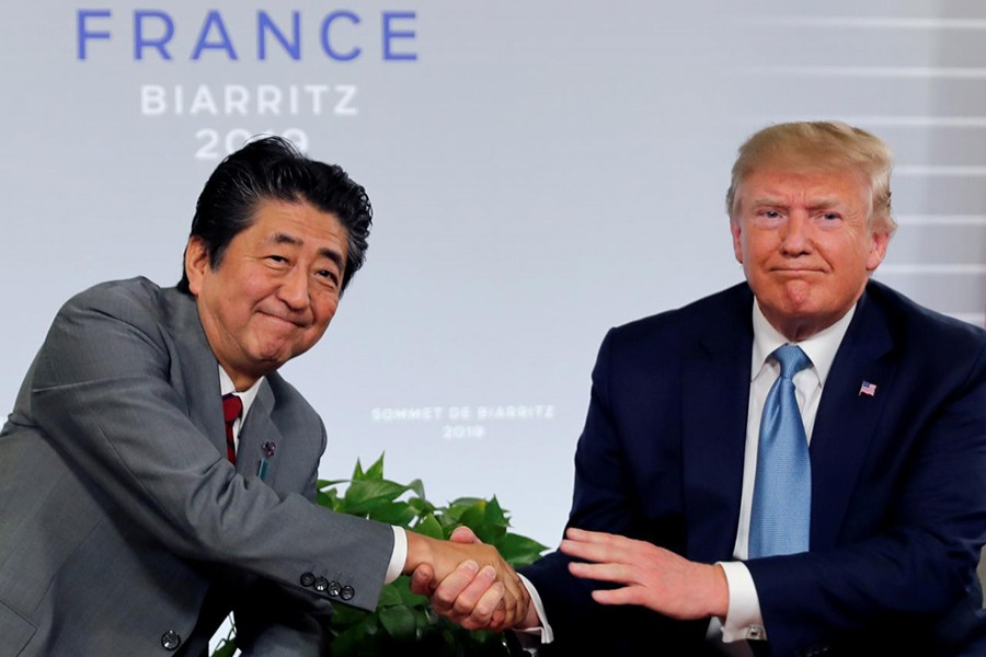 US President Donald Trump and Japan's Prime Minister Shinzo Abe shake hands at a bilateral meeting during the G7 summit in Biarritz, France on August 25, 2019 — Reuters/Files