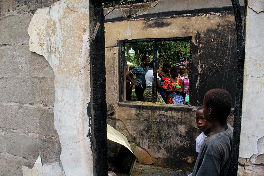 People walk through a burned building after a fire swept through a school killing children in Monrovia, Liberia on September 18, 2019 — Reuters photo