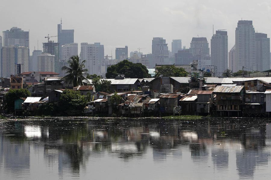 High-rise buildings are seen in the background with slum dwellings in the front, near a polluted river in Manila, the capital of the Philippines. -Reuters file photo